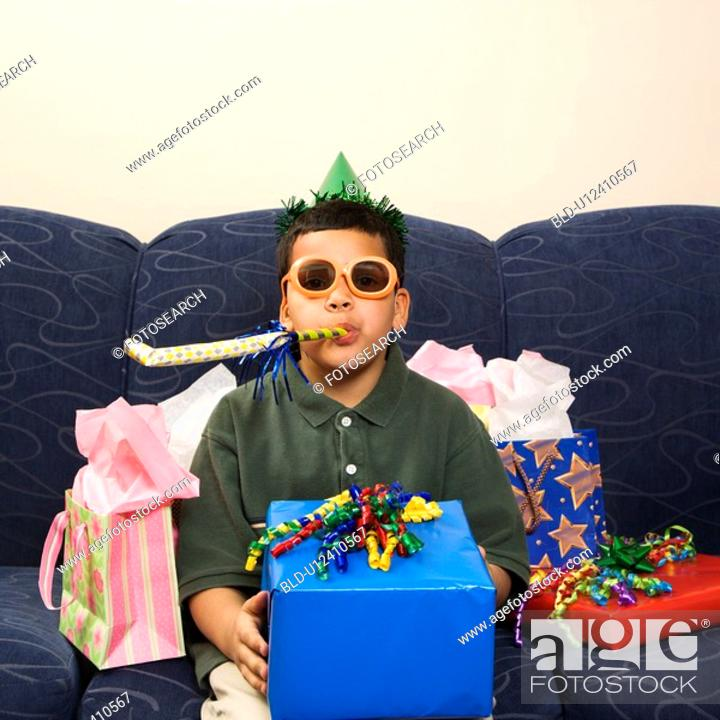 Stock Photo: Boy with birthday party favors and presents looking at viewer.