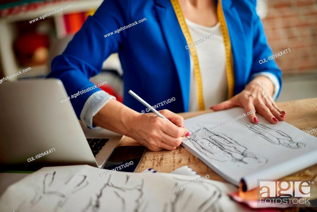 Stock Photo: Cropped view of woman sitting at desk sketching fashion design.
