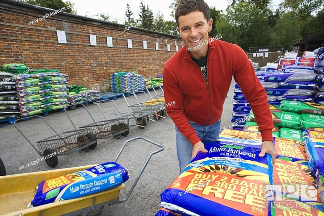 Stock Photo: Man loading compost into trolley in garden centre, smiling, portrait.