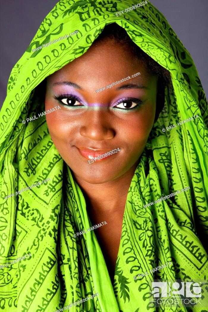 Stock Photo: The face of an innocent smiling beautiful young African-American woman with green headwrap and purple-green makeup, isolated.