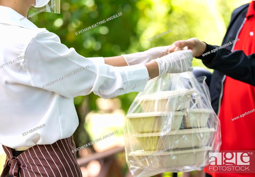 Stock Photo: Close up waitress hand give food box to deliverly man to deliver it to customer make online order. Food deliverly service concept in new normal after.