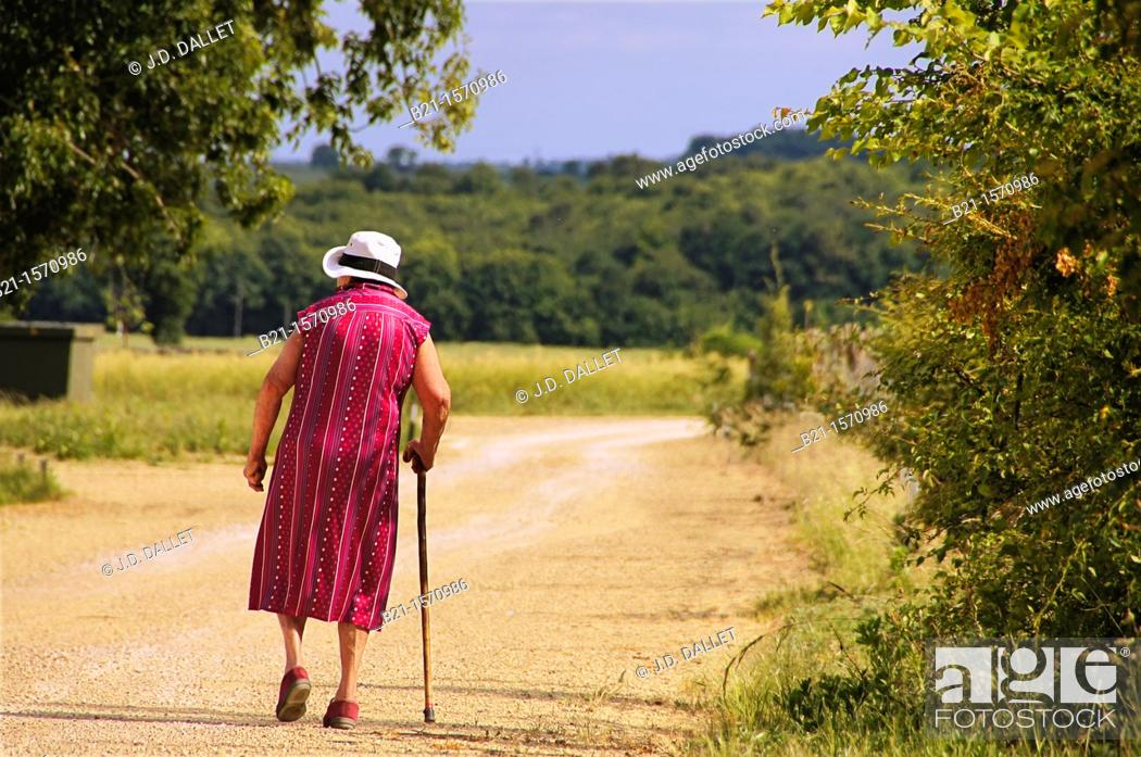 Stock Photo: France-Poitou Charente- Vienne- old lady walking with a stock.