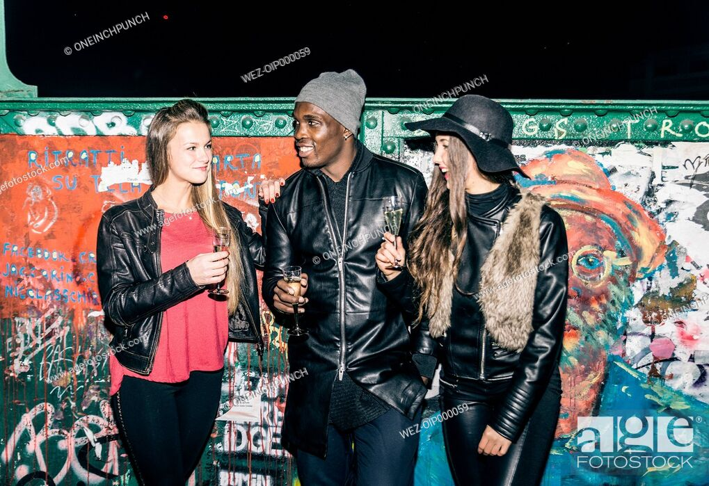 Stock Photo: Friends holding champagne glasses standing at graffiti wall at night.