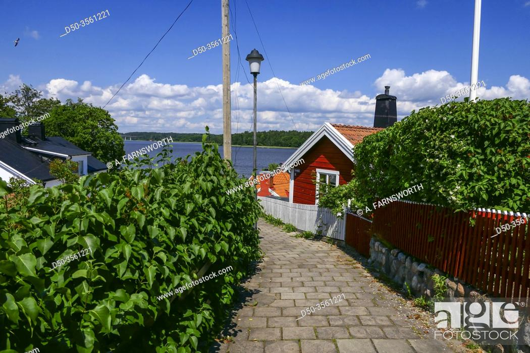 Imagen: Strangnas, Sweden A small red house on a path overlooking Lake Malaren.