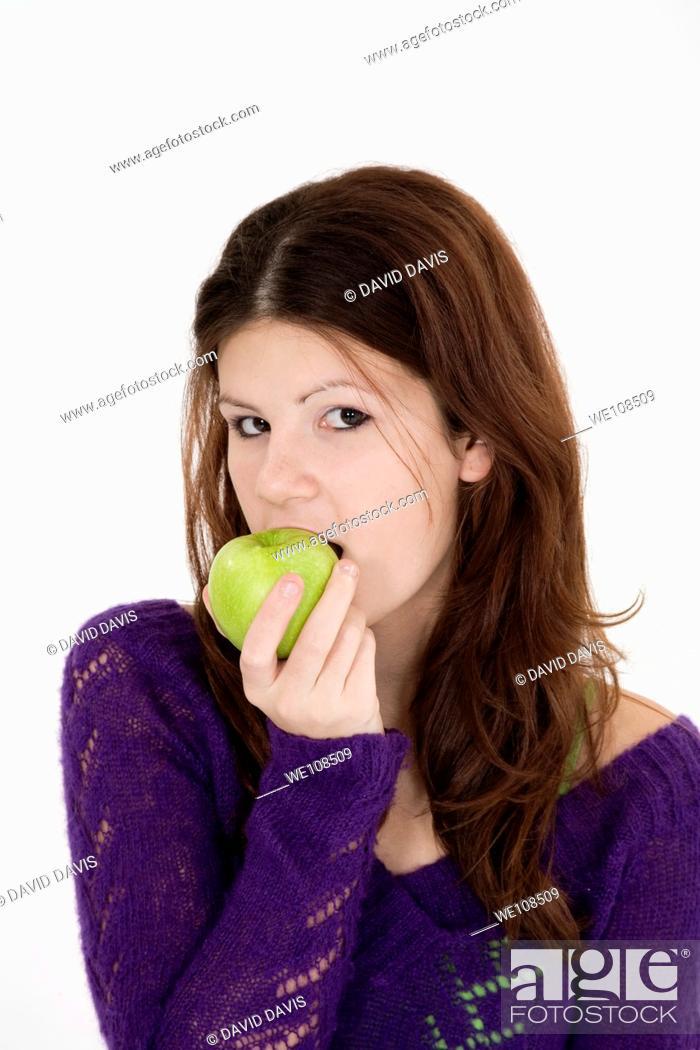 Stock Photo: Teenage girl eating a green apple.