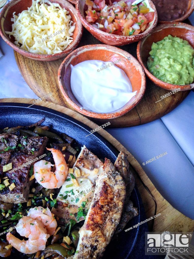 Stock Photo: Mexican Fajita Dish with beef steak strips, shrimp and chicken served in a hot cast iron skillet next to a tray of side dishes like sour cream, refried beans.