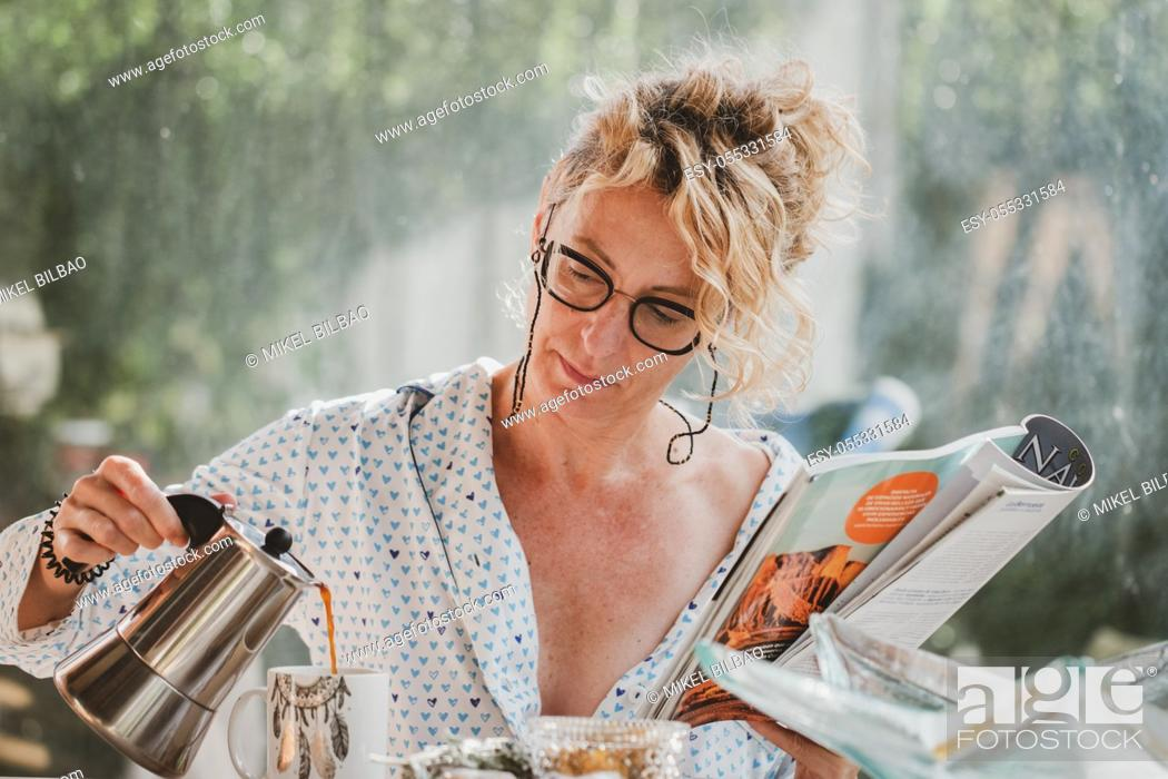 Photo de stock: Blonde young mature woman with glasses in pyjamas at home in breakfast time, reading a magazine and preparing a cup of coffee.