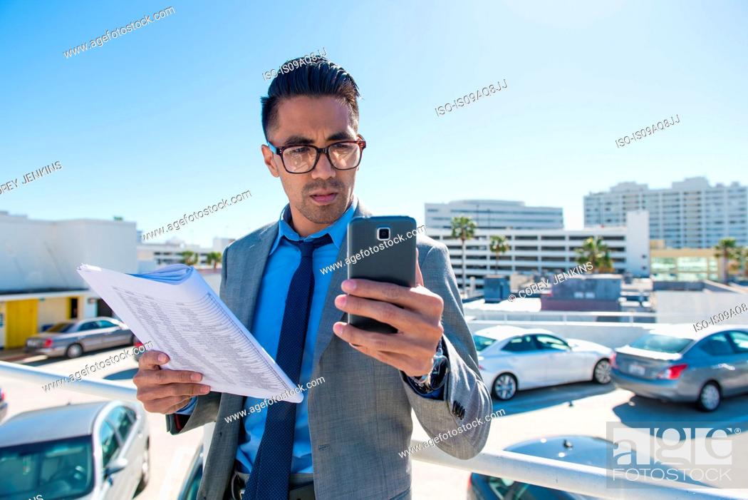 Stock Photo: Young businessman on city rooftop car park reading smartphone texts.