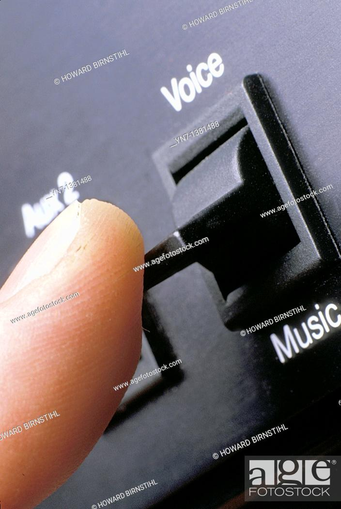 Stock Photo: close up of finger about to flick the switch in the recording studio from the vocal track to the music.