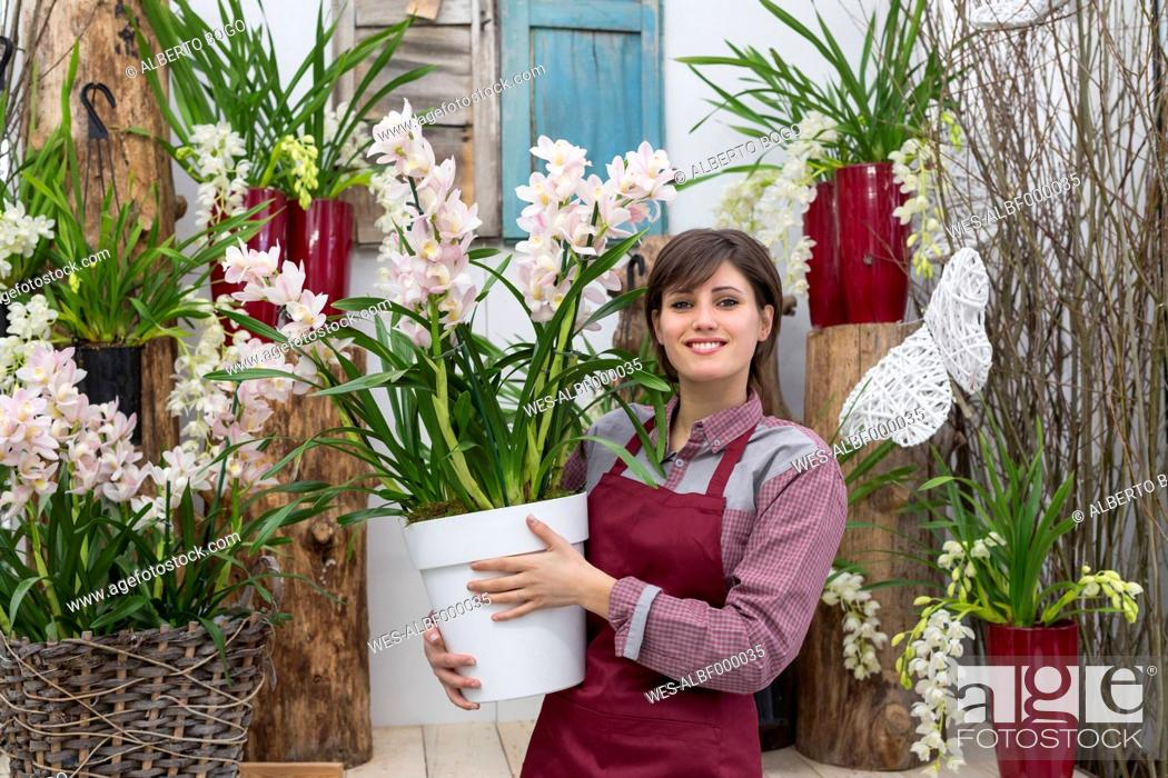Stock Photo: Young female gardener working in greenhouse, holding flowerpot.