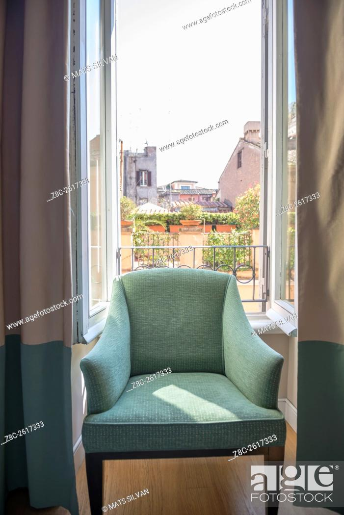 Stock Photo: Chair in a window with cityscape behind in Rome, Italy.