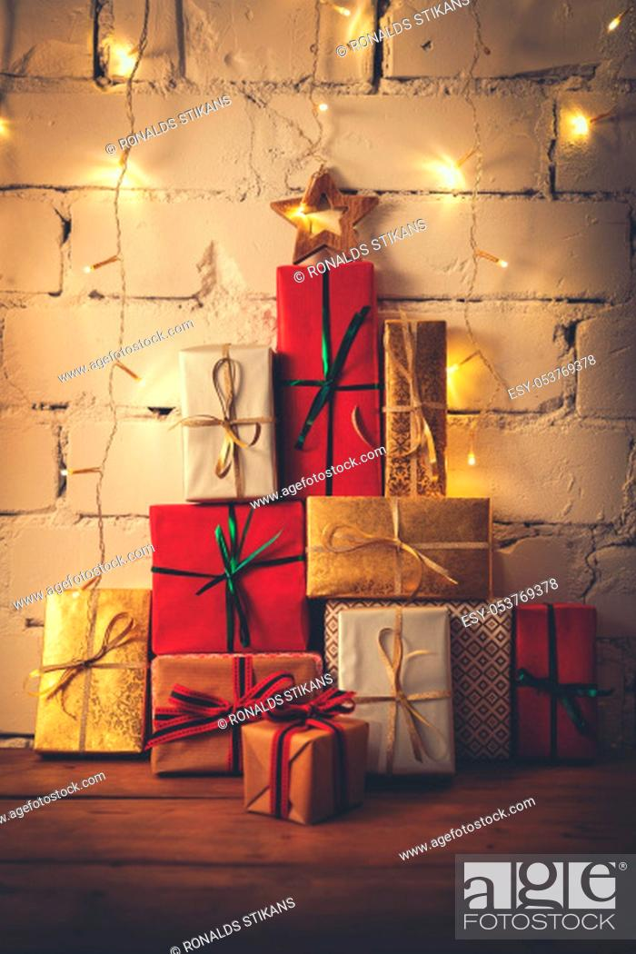 Stock Photo: stack of christmas gifts on white brick wall background.