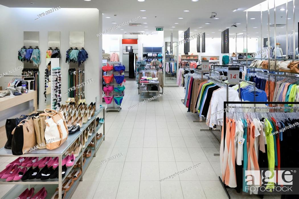 Stock Photo: Fashion shop interior with display. Clothing and bags in retail store. Large aisle and elevated view.