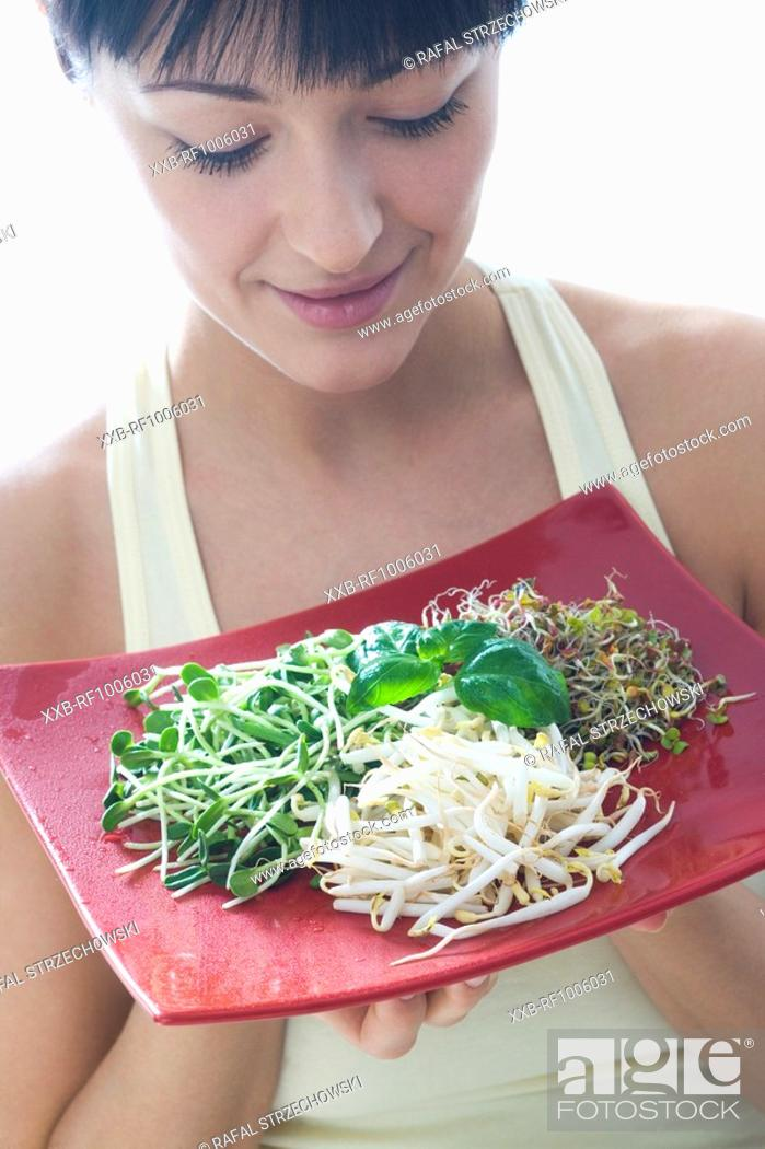 Stock Photo: toung woman with various sprouts on plate.