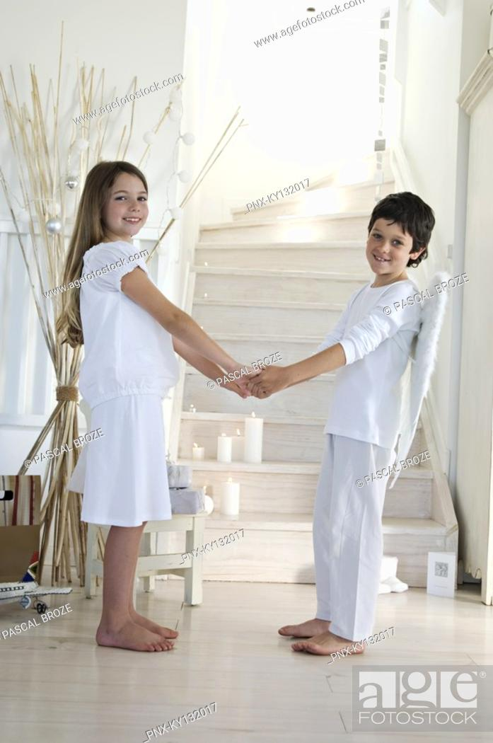 Stock Photo: Christmas day, girl and boy posing for the camera, holding their hands each others, indoors.