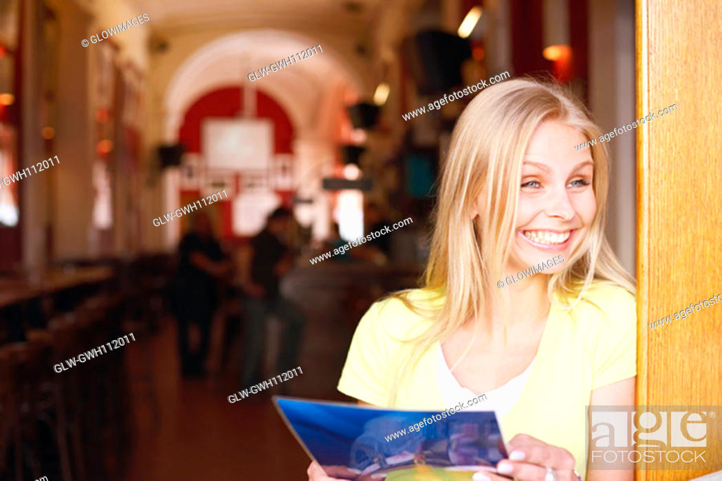 Stock Photo: Close-up of a young woman holding a menu card.