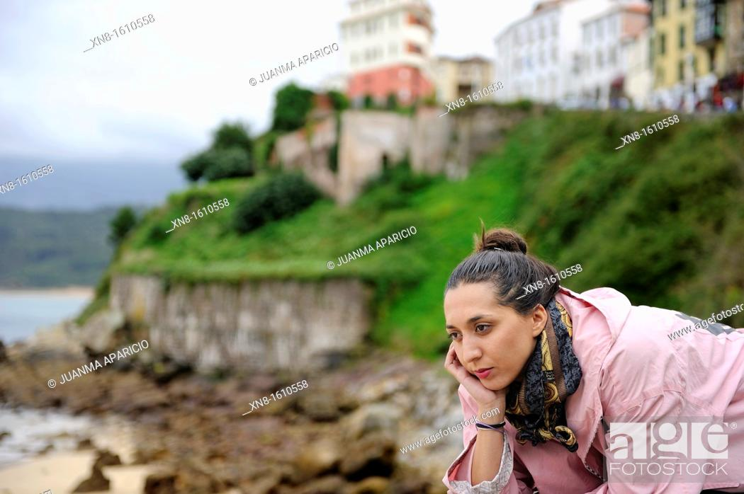 Stock Photo: small town on top of a hill and a beautiful young woman reclining facing the beach.