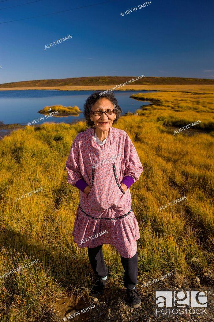 Imagen: Native Alaskan elder woman wearing an Atigik standing on the Tundra with a small lake in the background, Fall, Kotzbue, Arctic Alaska, USA.