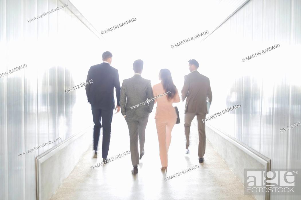 Imagen: Business people walking in illuminated office corridor.