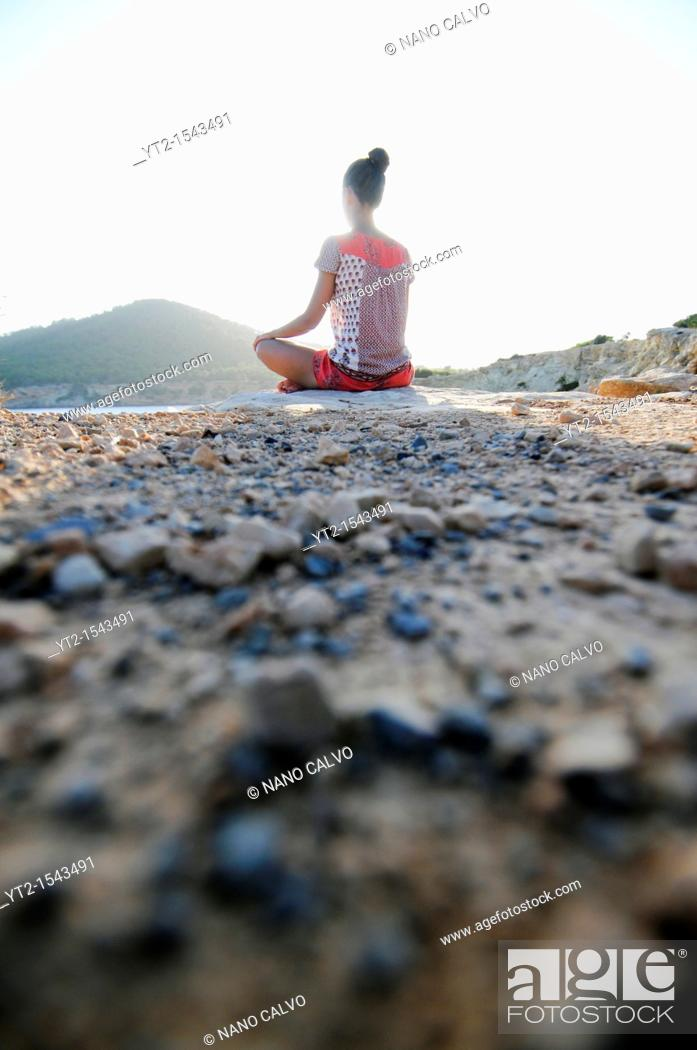 Stock Photo: Young woman meditating on a mountain.