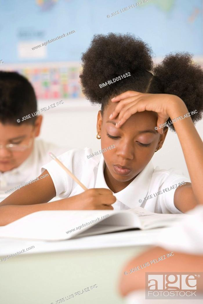 Stock Photo: African American girl writing at school desk.
