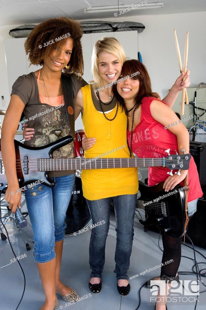 Stock Photo: Three teenage girls 15-17 in garage band, smiling, portrait.