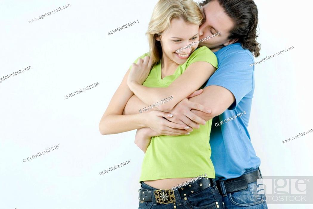 Stock Photo: Young man kissing a young woman's cheek.