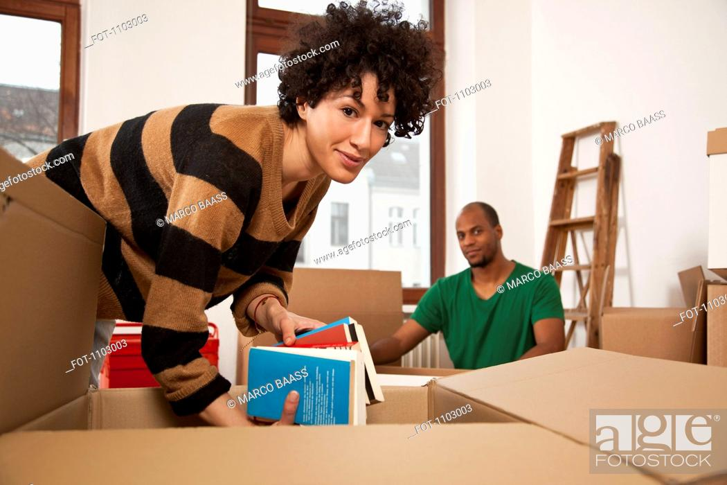 Stock Photo: A couple packing moving boxes.