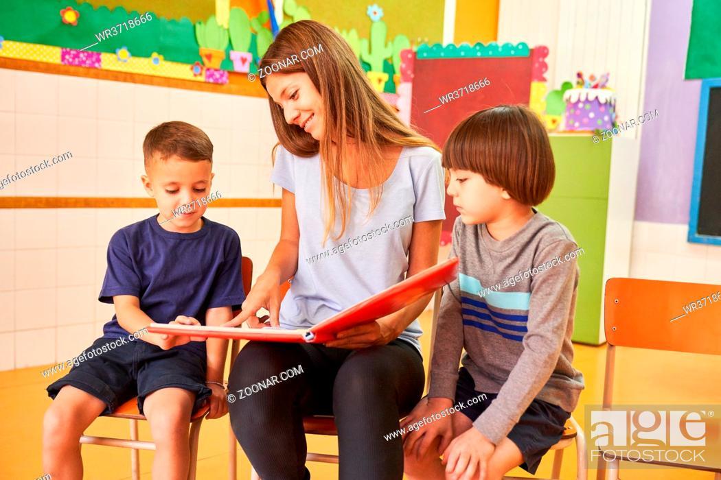 Stock Photo: Kindergärtnerin und zwei Kinder beim Buch vorlesen in der Kindertagesstätte oder Vorschule.