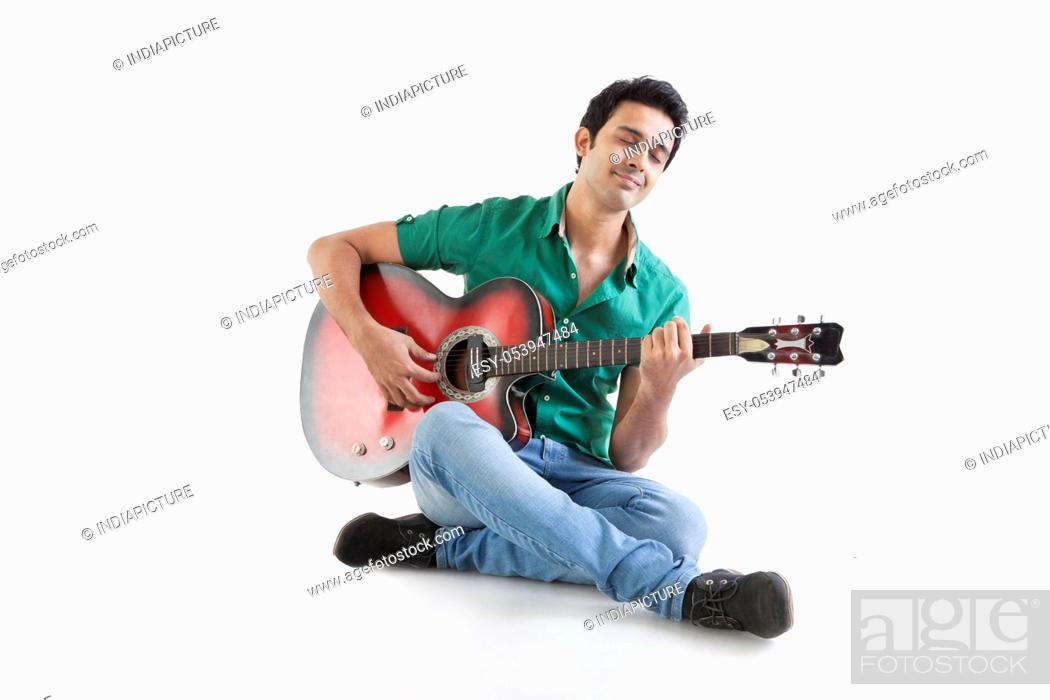 Stock Photo: Young man playing a guitar.