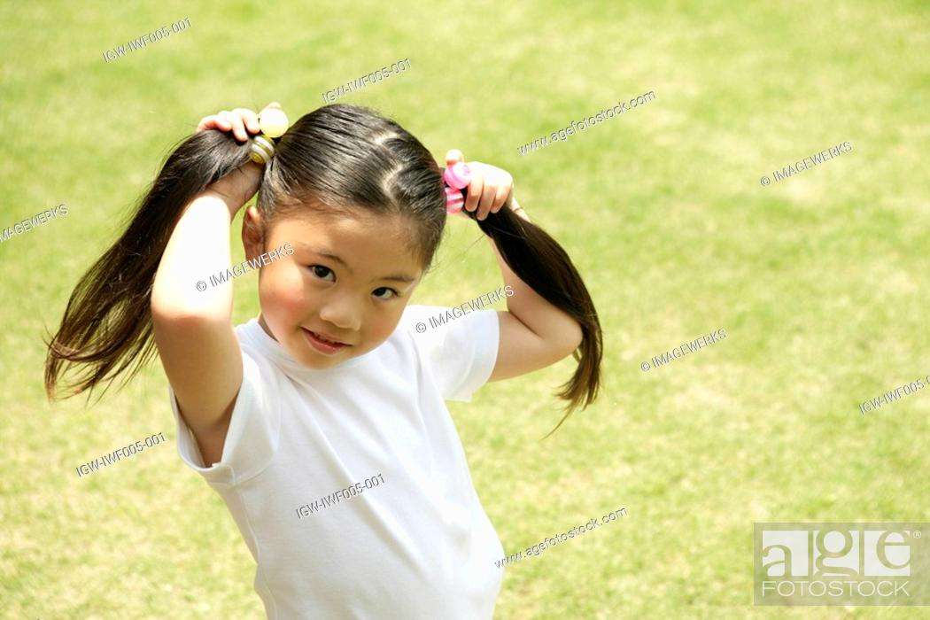 Stock Photo: A young girl showing her ponytails in front of the camera.