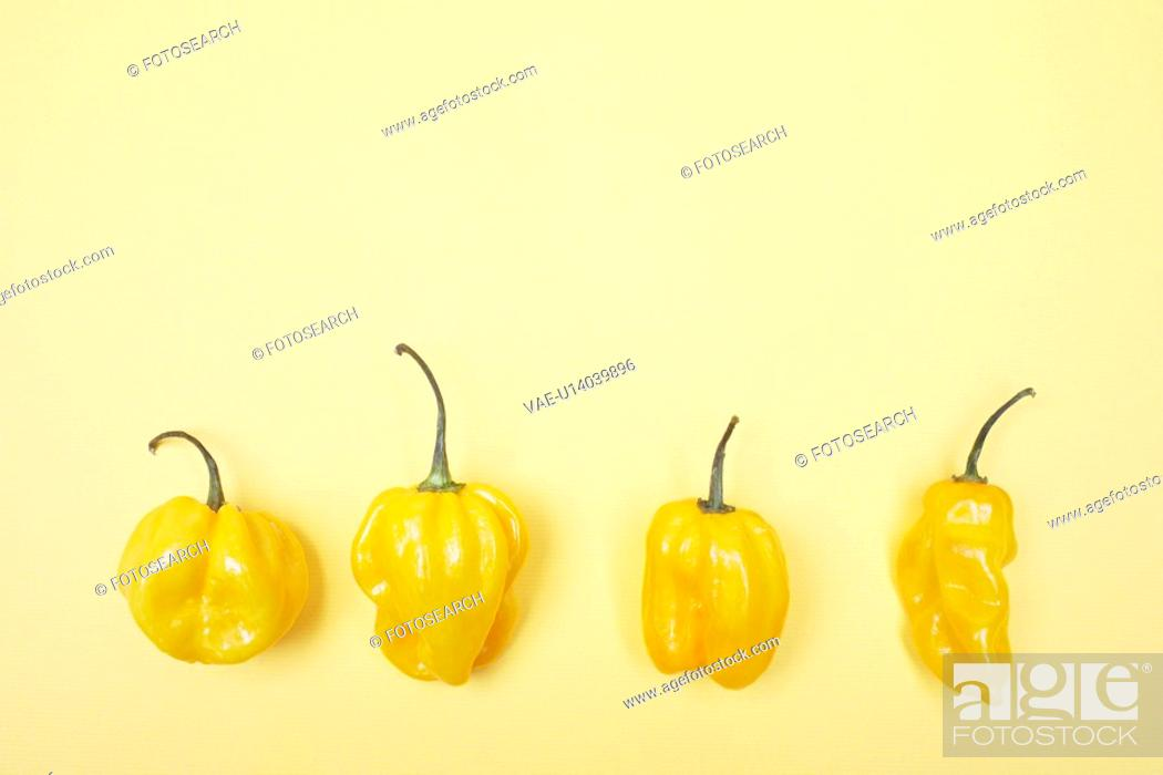 Stock Photo: Four yellow bell peppers in a row.