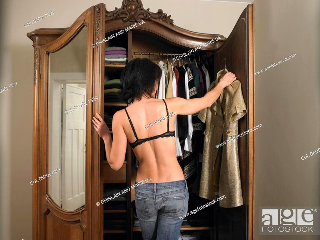 Stock Photo: Woman in bra, choosing her outfit.