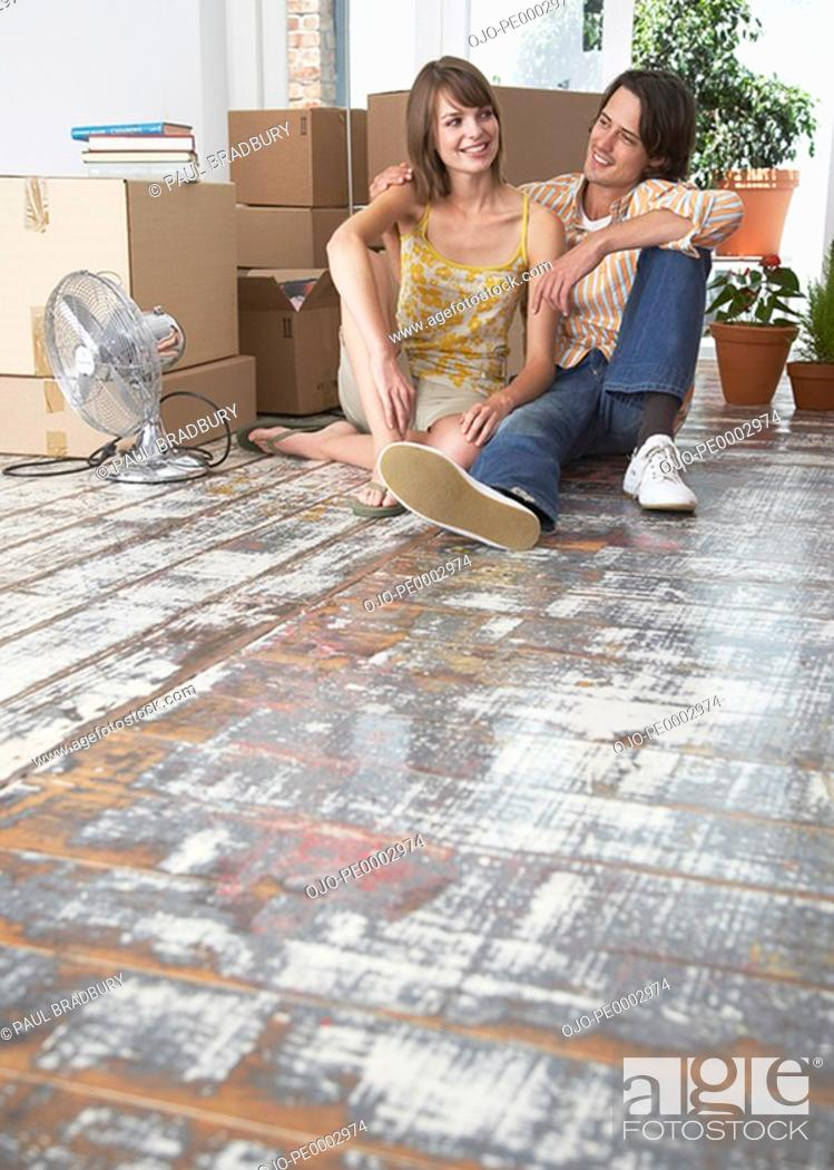 Stock Photo: Man and woman sitting on hardwood floor with cardboard boxes and fan.