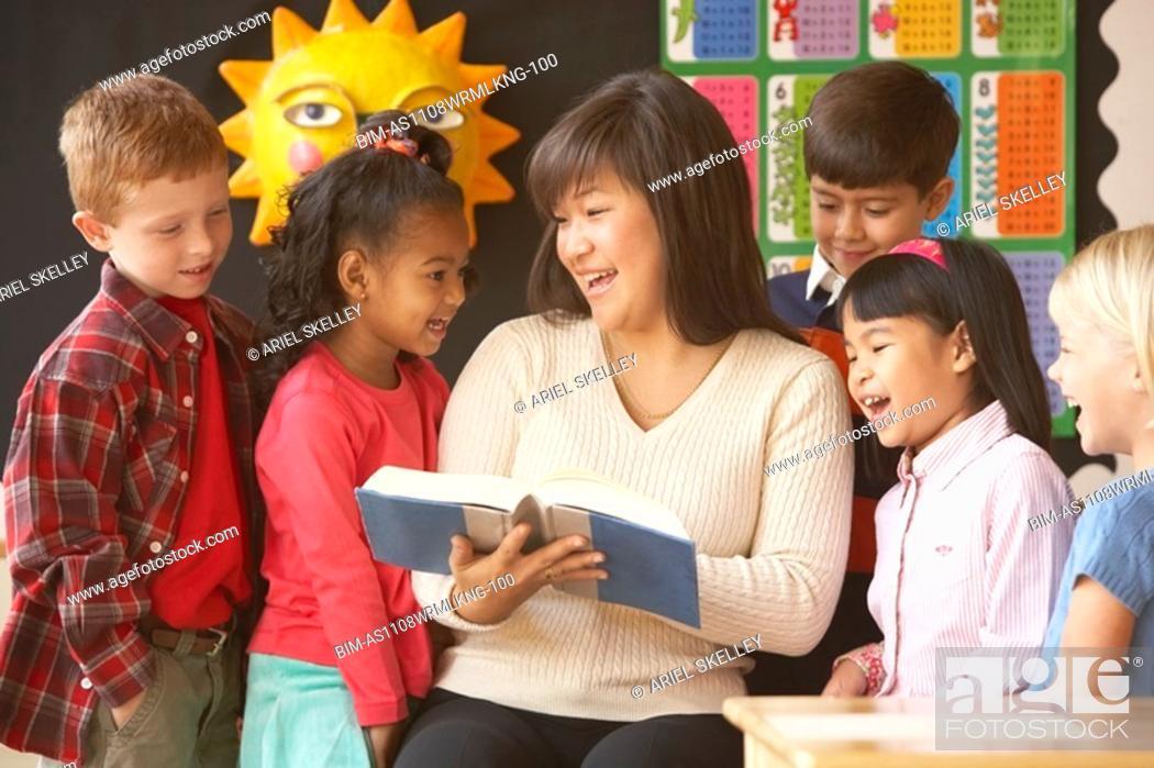 Stock Photo: Asian female teacher reading to students.