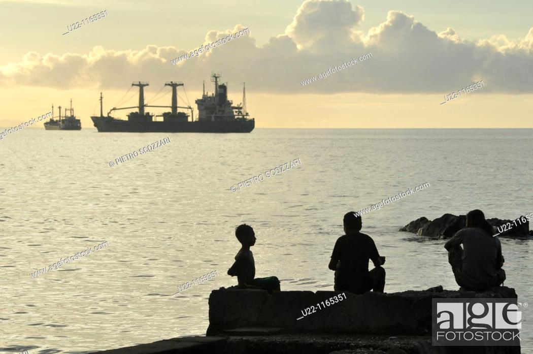 Stock Photo: Dili (East Timor): kids at the city's beach, near the harbor, at sunset.