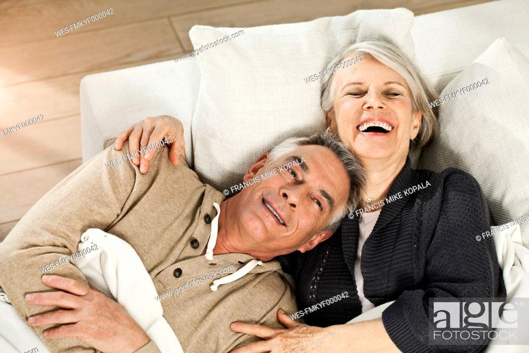 Stock Photo: Germany, Berlin, Senior couple lying on couch, smiling.