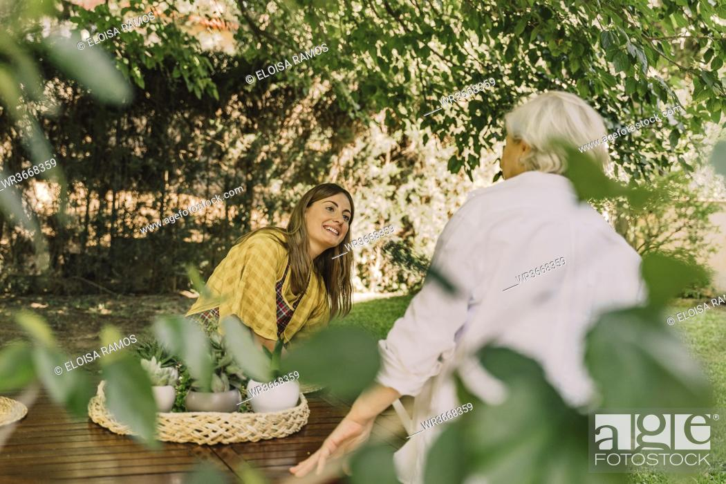 Imagen: Smiling woman talking with mother while sitting at table in yard.