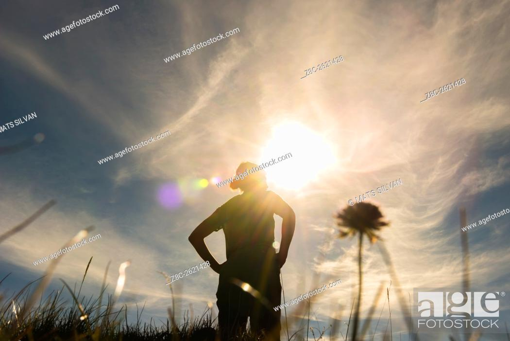 Stock Photo: Low angle view on a proud woman in backlit with sunshine and grass and flower in Grisons, Switzerland.