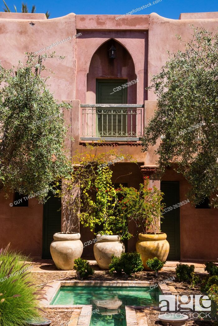 Stock Photo: Typical moroccan architecture, riad adobe walls , fountain and flower pots, Morocco.