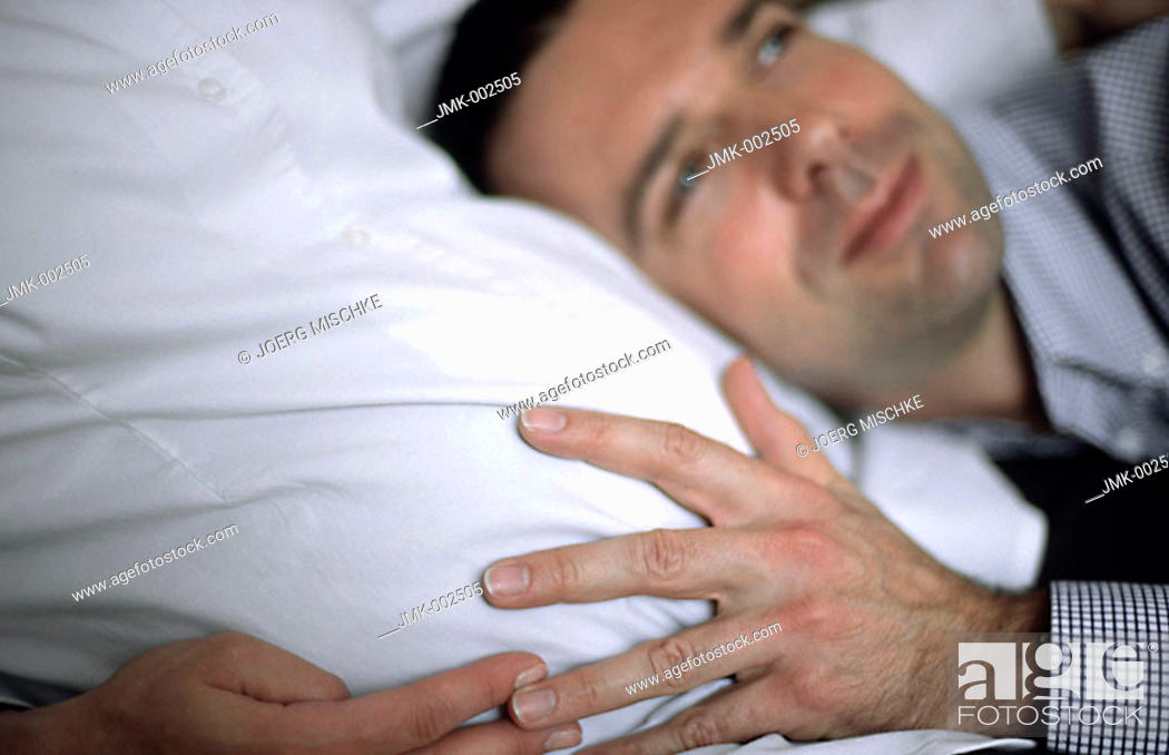 Stock Photo: A young man harking to his unborn child and young pregnant woman, 25-30 30-35 35-40 years old.