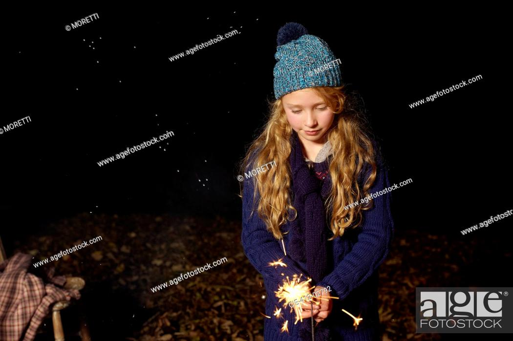 Stock Photo: Girl playing with sparkler outdoors.