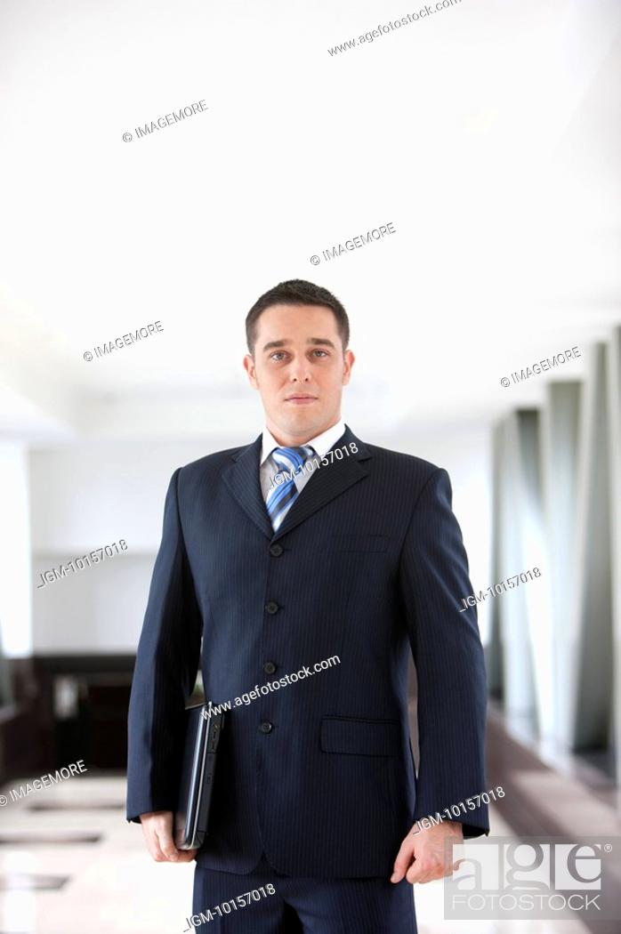 Stock Photo: Business people standing with laptop and looking at the camera.
