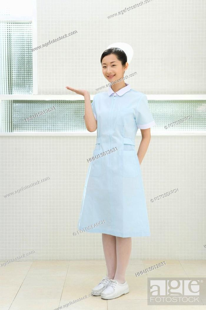 Stock Photo: Portrait of a nurse, smiling and looking at camera, front view.