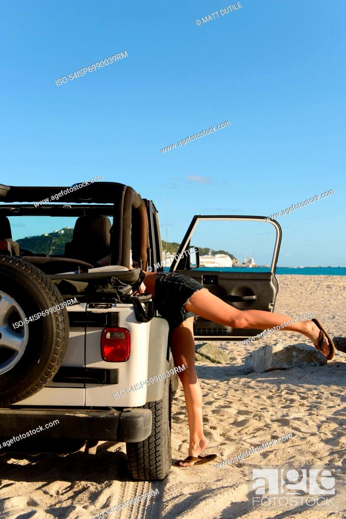 Stock Photo: Woman searching in jeep on beach.