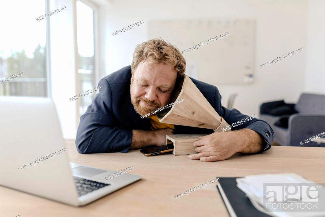 Stock Photo: Businessman in office listening to music with a wooden gramophone.