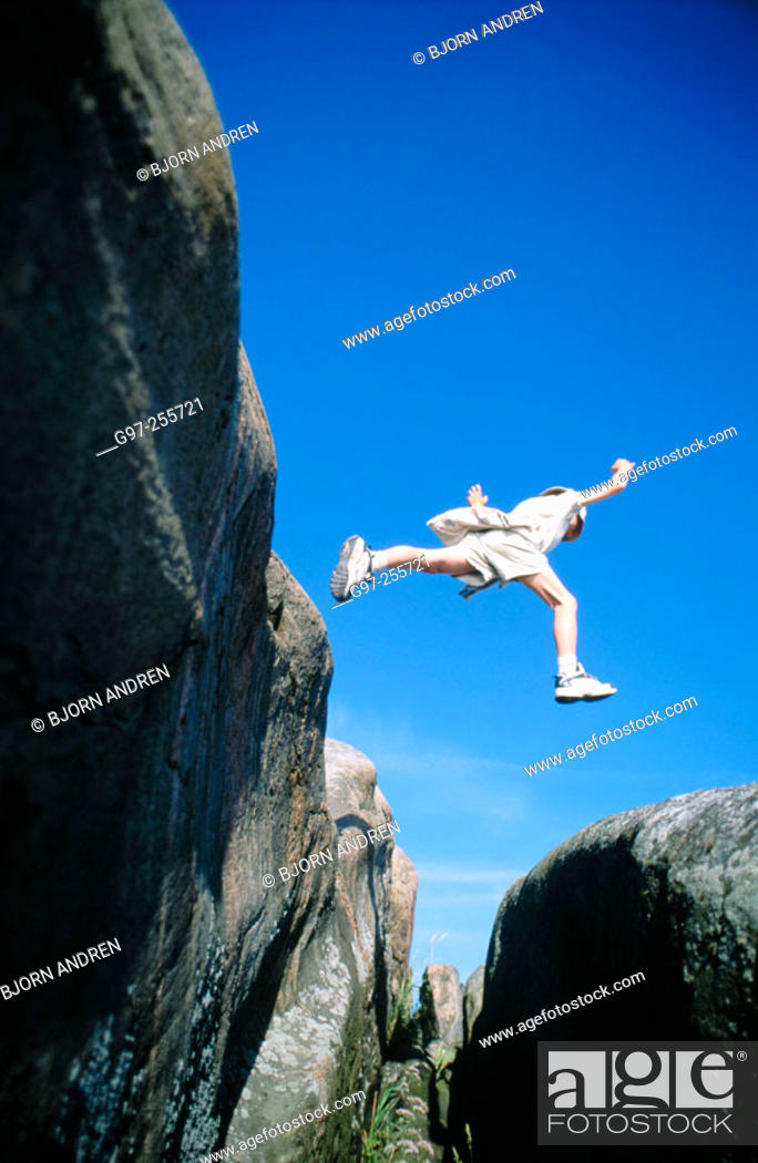 Stock Photo: Boy jumping over abyss.