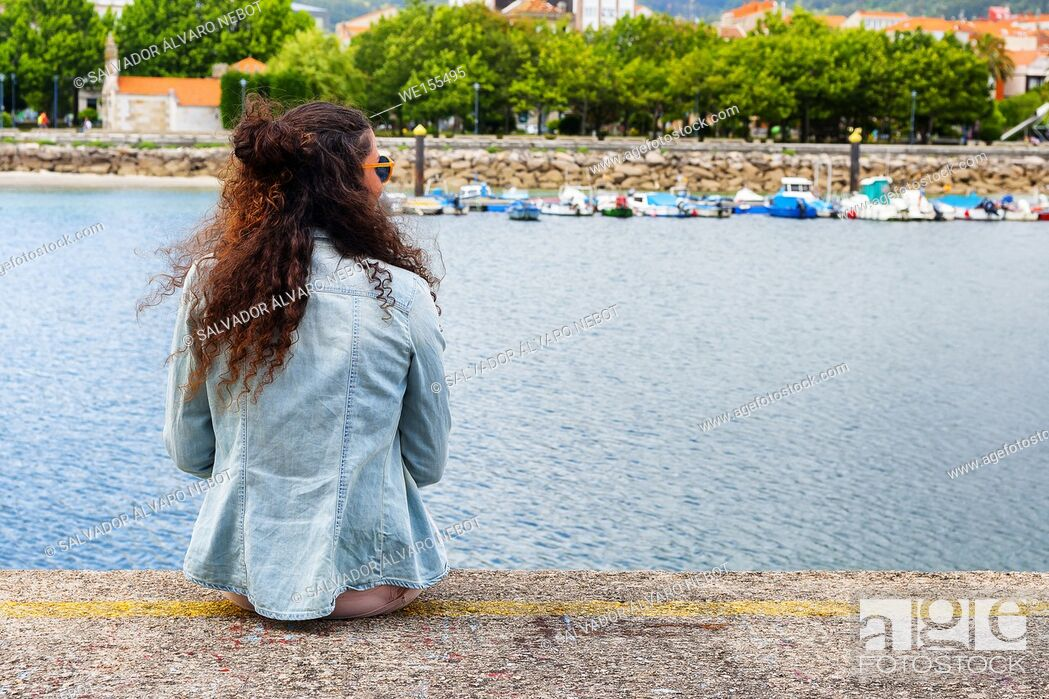Stock Photo: Young girl sitting in the port of Cangas de Morrazo, Pontevedra, Spain, Europe.