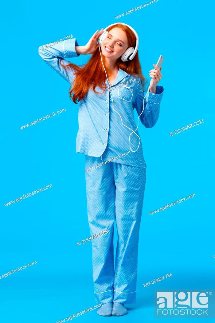 Stock Photo: What beautiful morning to listen favorite playlist. Vertical full-length portrait tender redhead woman in pyjama, holding smartphone.