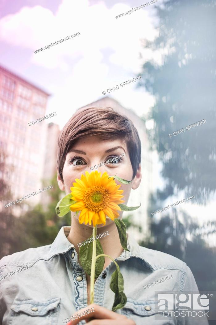 Stock Photo: Woman covering mouth with flower.
